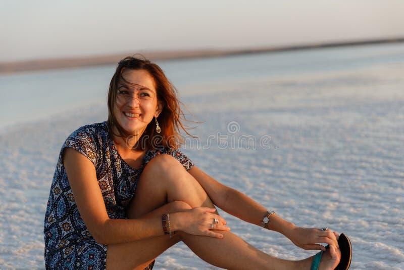 Счастливая усмехаясь девушка наслаждаясь солнцем захода солнца и трясет ее голову, сидит на соли стоковое изображение rf