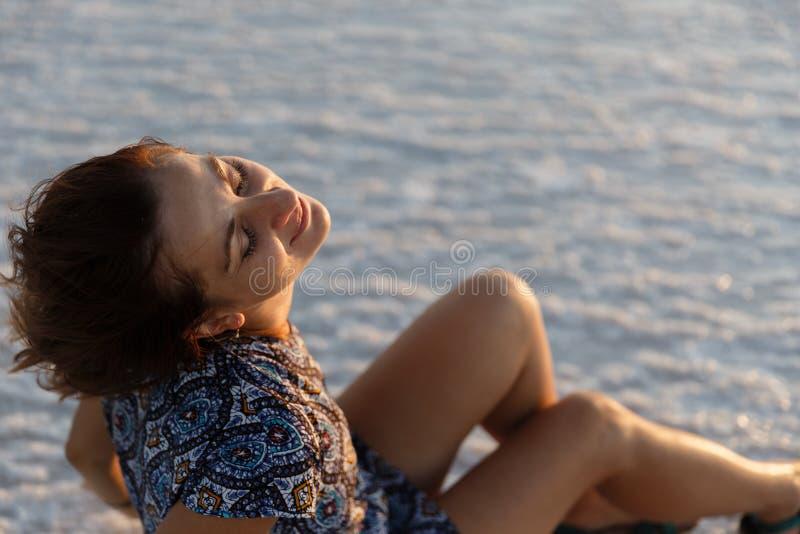 Счастливая усмехаясь девушка наслаждаясь солнцем захода солнца и трясет ее голову, сидит на соли стоковая фотография rf
