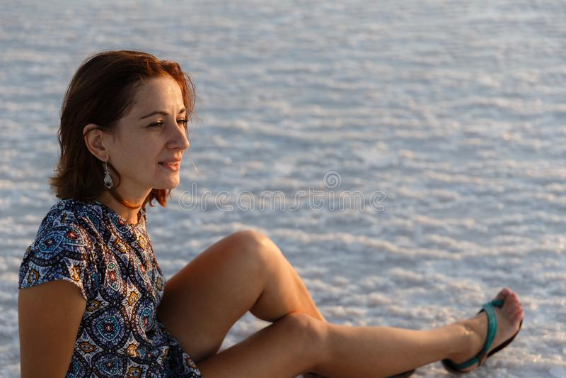 Счастливая усмехаясь девушка наслаждаясь солнцем захода солнца и трясет ее голову, сидит на соли стоковое фото