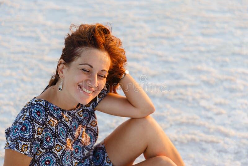 Счастливая усмехаясь девушка наслаждаясь солнцем захода солнца и трясет ее голову, сидит на соли стоковые фотографии rf