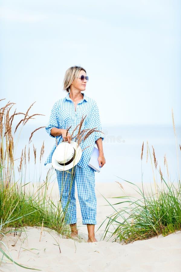 Счастливая усмехаясь женщина в солнечных очках держа положение книги на песке взморья Изображение конца-вверх летнего времени Out стоковая фотография rf