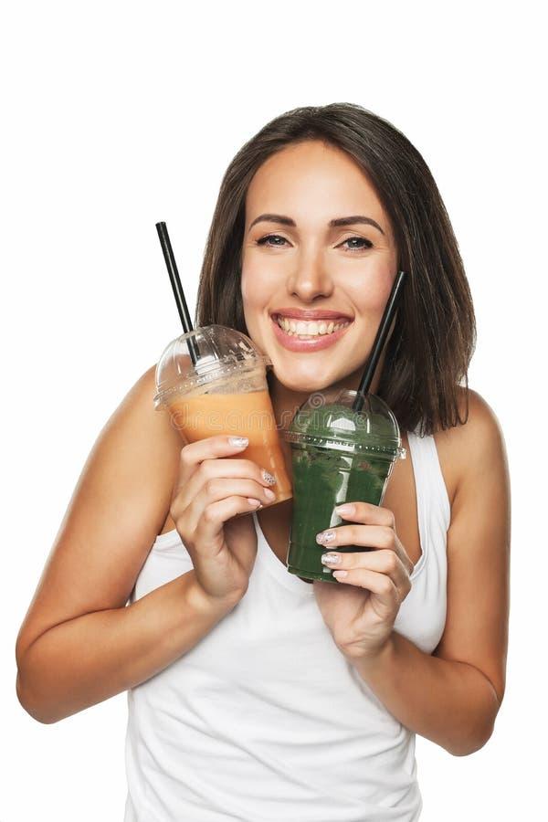 Счастливая усмехаясь женщина держа smoothie изолированный на белизне стоковое фото rf