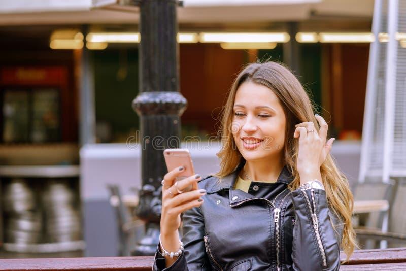 Счастливая усмехаясь женщина используя смартфон на улице стоковые изображения