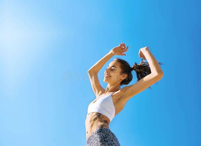 Счастливая усмехаясь женщина с загоренным тонким телом и татуировка представляя против голубого неба стоковые фотографии rf