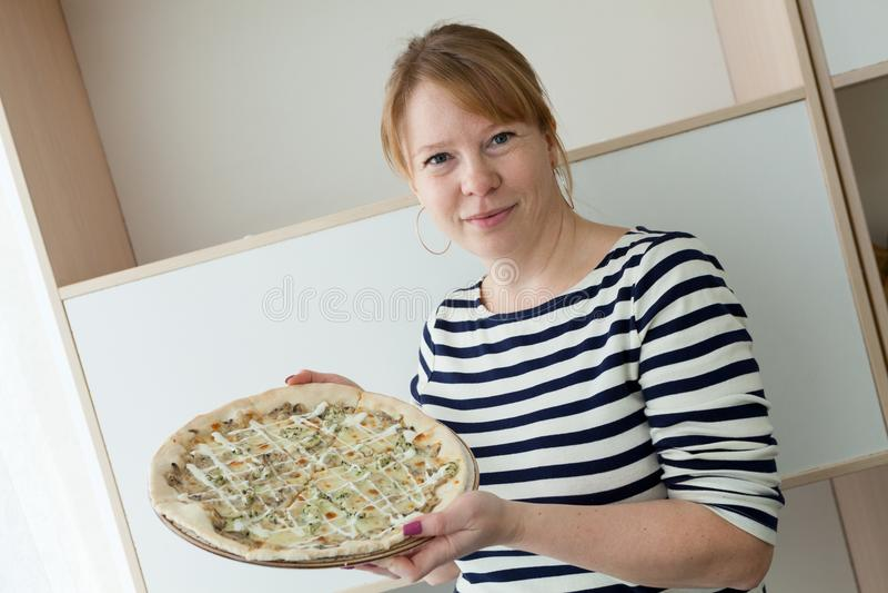 Счастливая усмехаясь кавказская женщина держа пиццу на белой плите стоковая фотография rf