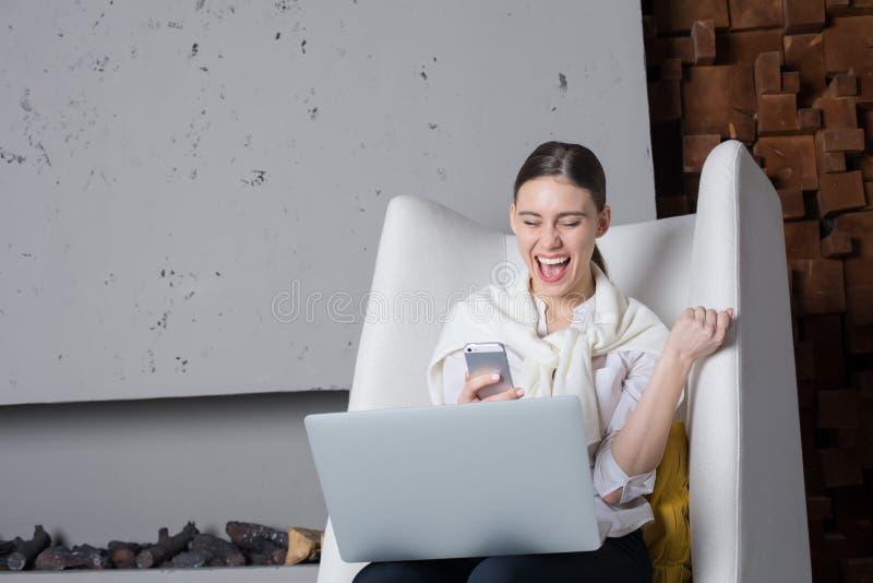 Счастливая усмехаясь коммерсантка получила положительное сообщение на мобильном телефоне о успешном принятии ее новый проект, сид стоковые фотографии rf
