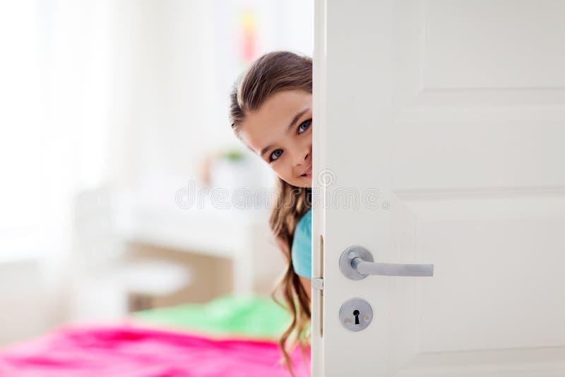 Счастливая усмехаясь красивая девушка за дверью дома стоковое фото rf
