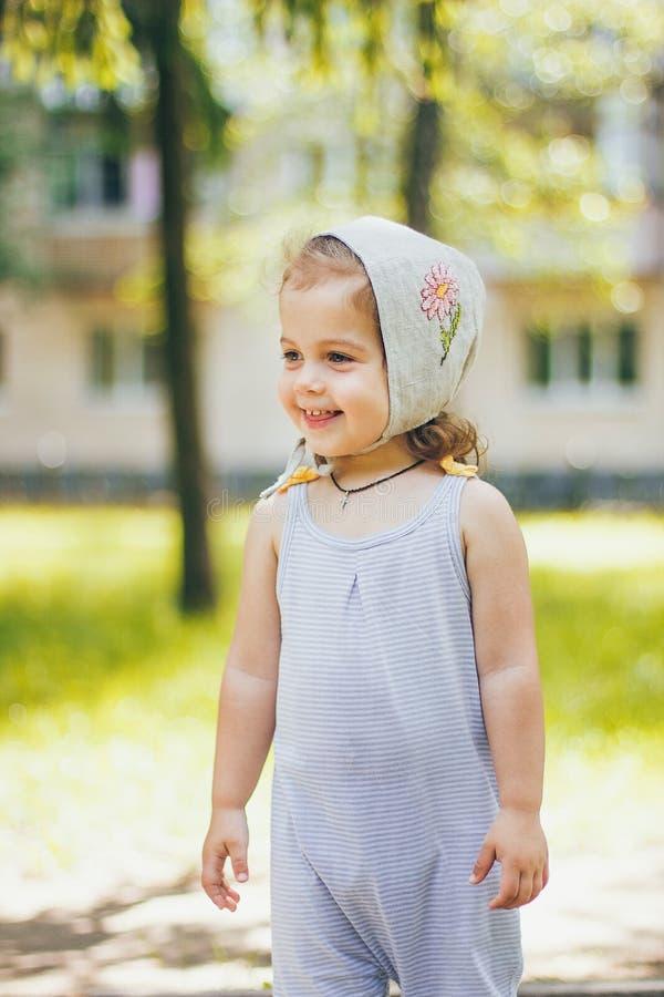 Счастливая усмехаясь красивая маленькая девочка в striped одежды и шляпа солнца в солнечном парке outdoors стоковые изображения