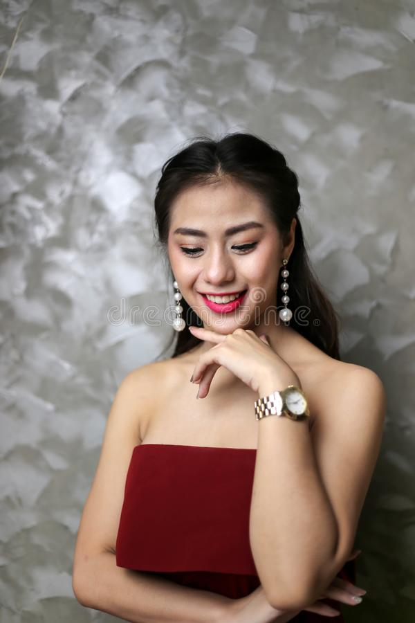 Счастливая усмехаясь красивая молодая сексуальная женщина в красном платье партии стоковые фото