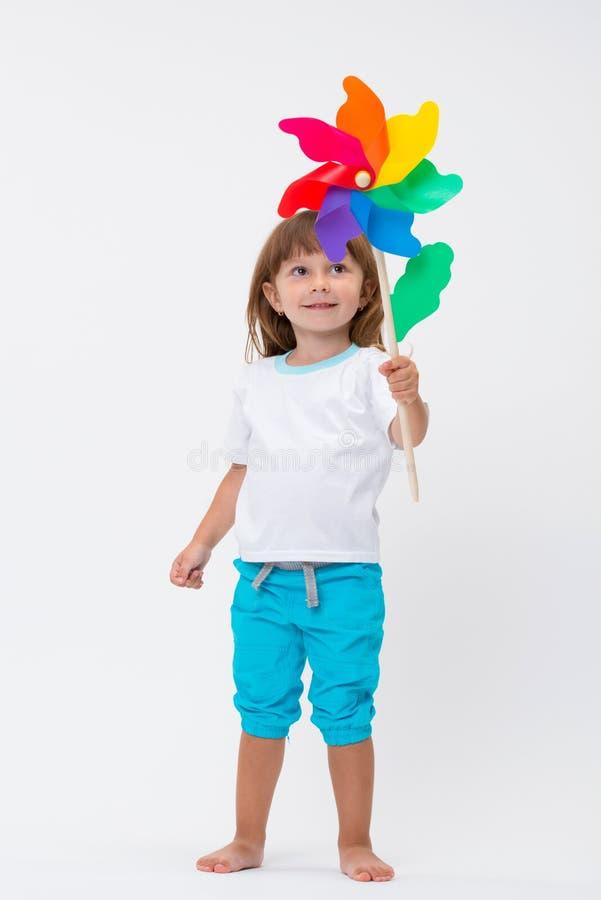 Счастливая усмехаясь маленькая девочка держа красочную ветрянку pinwheel игрушки изолированный на белой предпосылке стоковые фото
