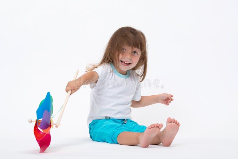 Счастливая усмехаясь маленькая девочка держа красочную ветрянку pinwheel игрушки изолированный на белой предпосылке стоковое фото rf