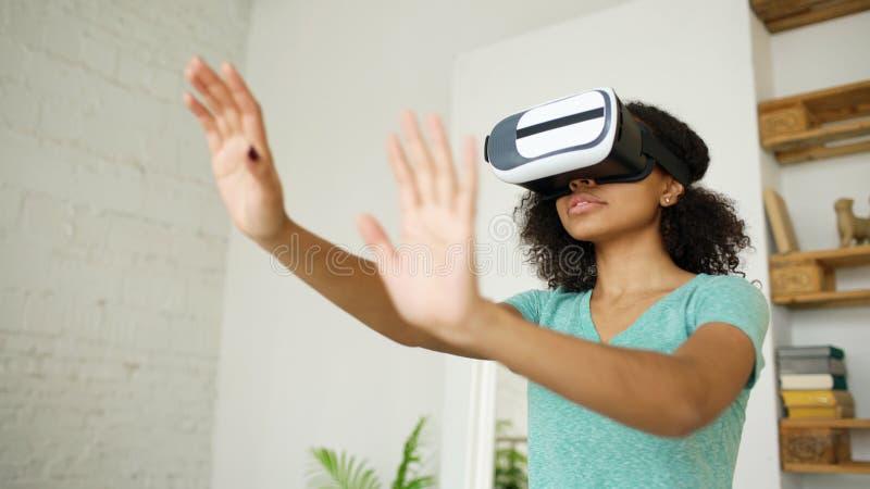 Счастливая усмехаясь молодая девушка смешанной гонки получая опыт используя стекла шлемофона VR виртуальной реальности и moving р стоковое фото