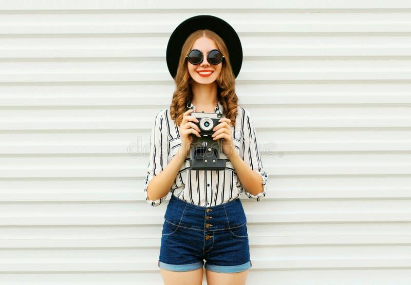 Счастливая усмехаясь молодая женщина держа винтажную камеру фильма в черной круглой шляпе, шортах, белой striped рубашке на белой стоковые изображения rf
