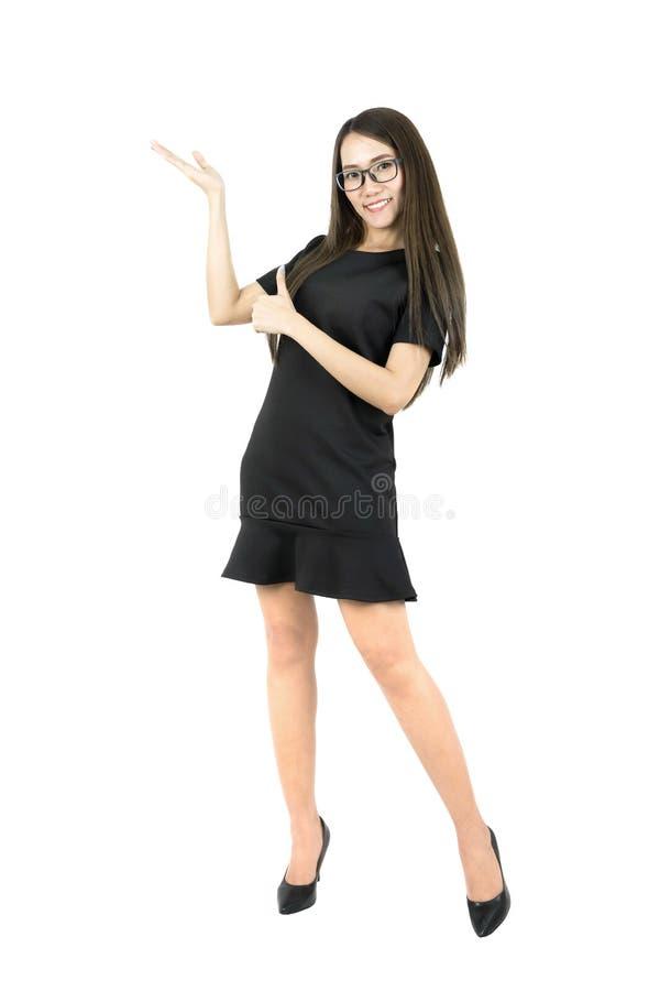 Счастливая усмехаясь молодая красивая азиатская бизнес-леди представляя что-то и большой палец руки вверх по полному телу стоковые изображения