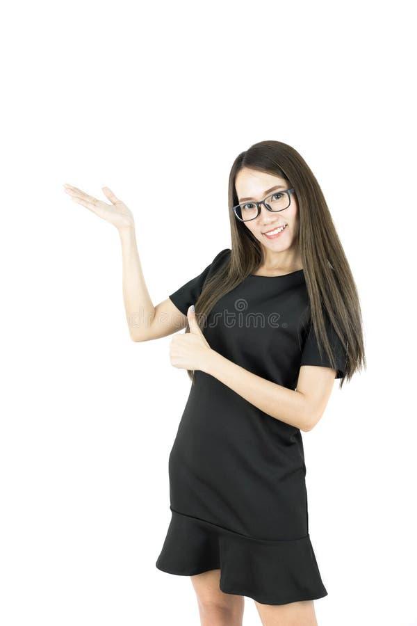 Счастливая усмехаясь молодая красивая азиатская бизнес-леди представляя что-то и большой палец руки вверх стоковая фотография rf