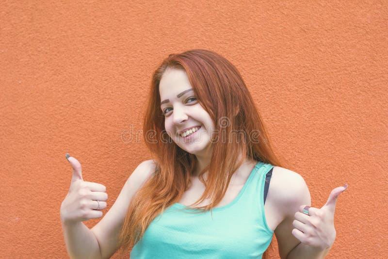 Счастливая усмехаясь рыжеволосая женщина показывая большие пальцы руки вверх стоковое фото