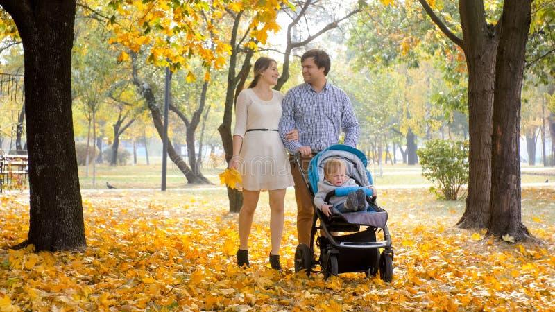 Счастливая усмехаясь семья при мальчик ребёнка в pram идя на желтый цвет выходит на парк осени стоковое фото rf