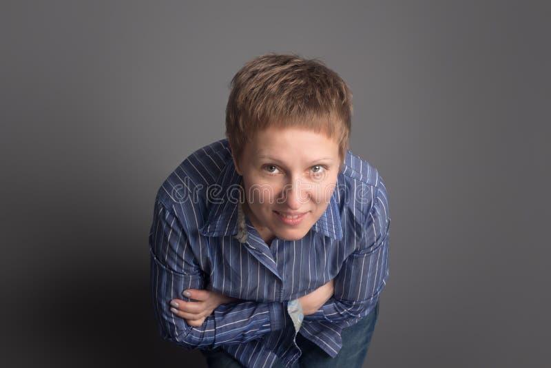Счастливая усмехаясь средн-постаретая женщина в голубой рубашке стоковое фото rf