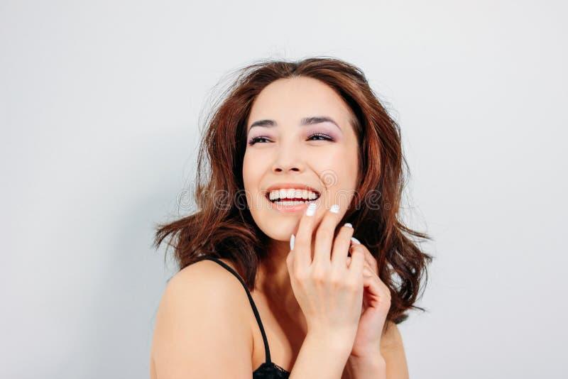 Счастливая чувственная усмехаясь молодая женщина девушки азиатская с темным длинным вьющиеся волосы в черном нижнем белье на бело стоковая фотография rf