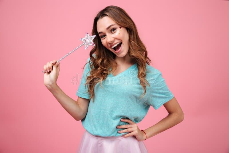 Счастливая эмоциональная молодая женщина держа волшебно звезду ручки стоковые фото