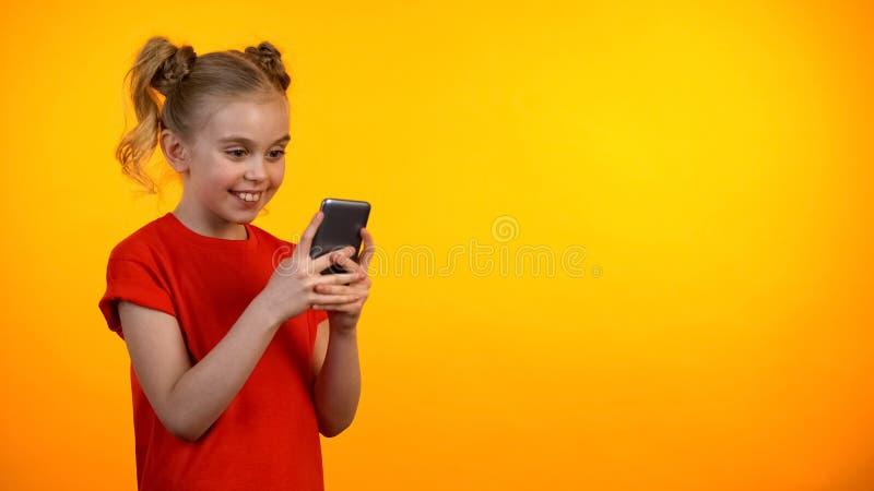 Счастливая preteen девушка перечисляя смартфон и усмехаясь, воспитательное приложение, устройство стоковое изображение