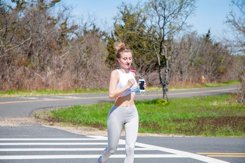 Счастливая sporty женщина бежать и слушая к музыке стоковое изображение