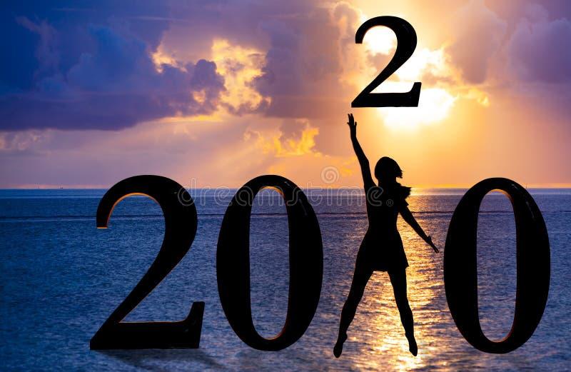 Счастливого нового года смешанной медиа-карты 2020 — прыжок женщины силуэт над морем в рамках номера 2020 года с закатом фона стоковая фотография