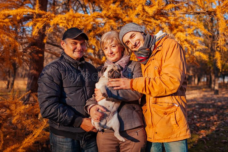 Счастливое время траты семьи с собакой мопса в парке осени Родители с их сыном обнимая любимца Семейные ценности стоковая фотография