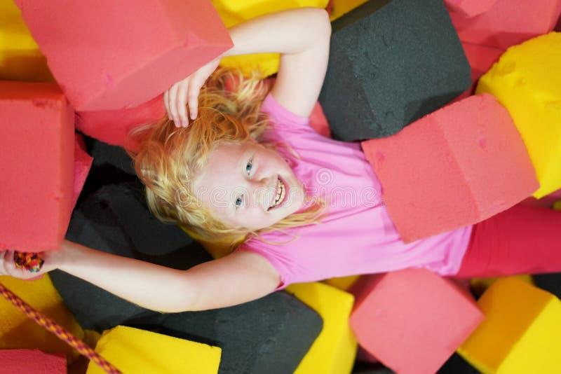 Счастливое детство современного ребенка в городе - девушка лежит в мягких кубах в парке атракционов стоковое фото rf