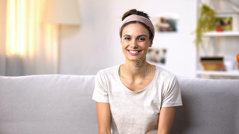 Счастливое женское усаживание на софе и смотреть камеру, здоровые зубы и кожу стоковые изображения