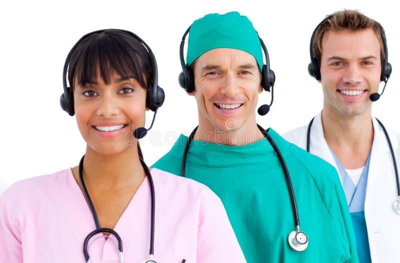 счастливое использование медицинской бригады шлемофонов стоковая фотография rf