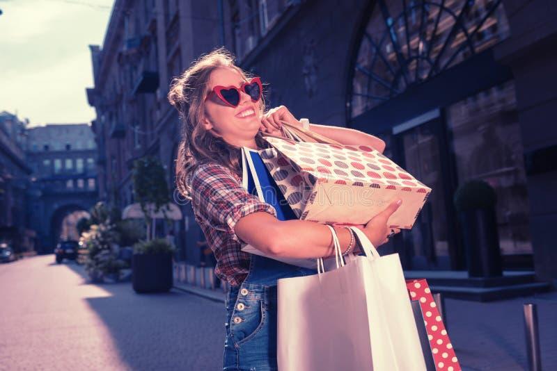 Счастливое испуская лучи стильное shopaholic удерживание ее тяжелые хозяйственные сумки стоковое фото