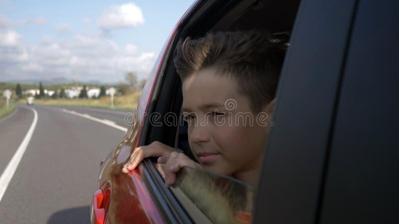 Счастливое катание мальчика в автомобиле с открытым окном и смотреть снаружи, ветер развивает волосы стоковое фото rf