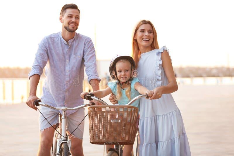 Счастливое катание семьи bicycles outdoors стоковое фото