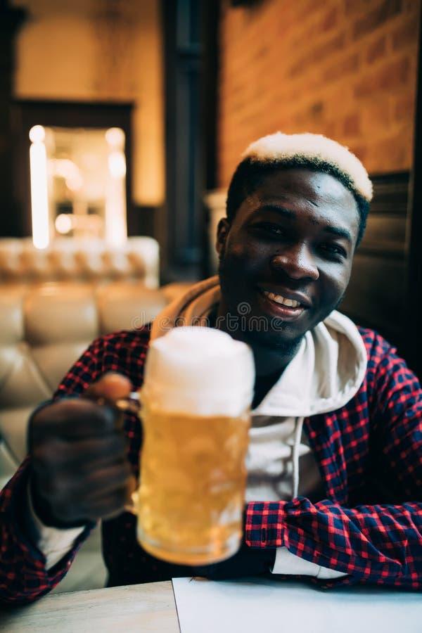 Счастливое красивое Афро-американское пиво молодого человека выпивая в пабе стоковое изображение