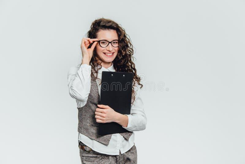 Счастливое красивое молодое положение бизнес-леди Удержание доски сзажимом для бумаги над белой предпосылкой стоковые фото
