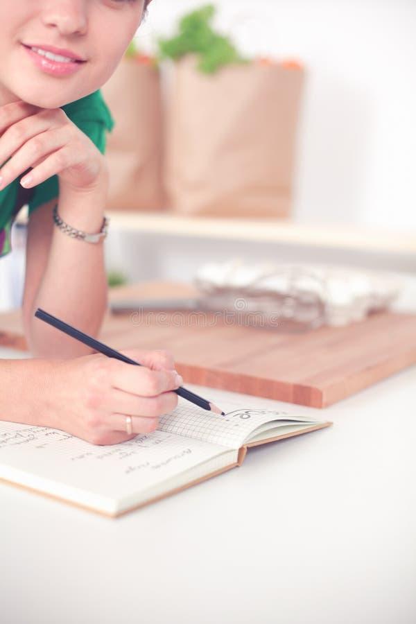 Счастливое красивое положение женщины в ее кухне писать на тетради дома стоковое фото rf