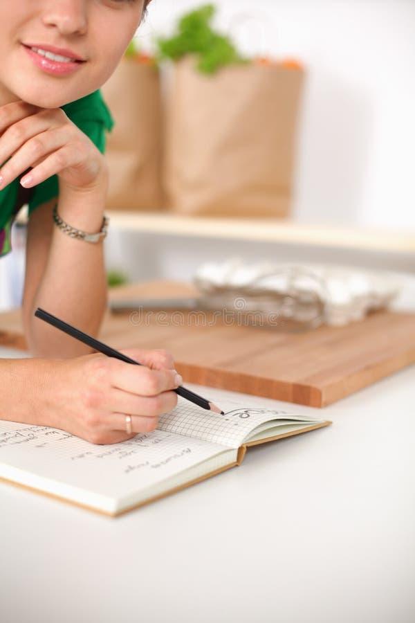Счастливое красивое положение женщины в ее кухне писать на тетради дома стоковые фото