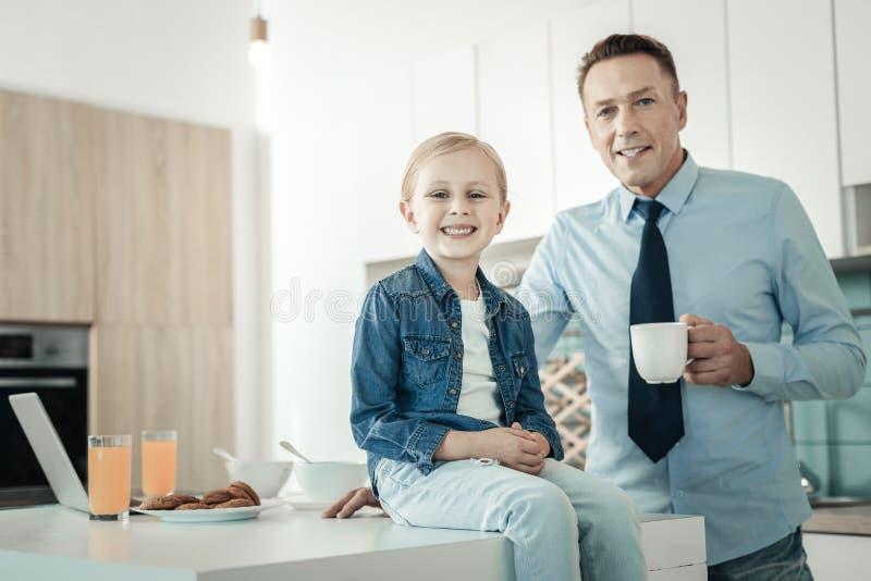 Счастливое маленькое женское усаживание на таблице стоковые изображения