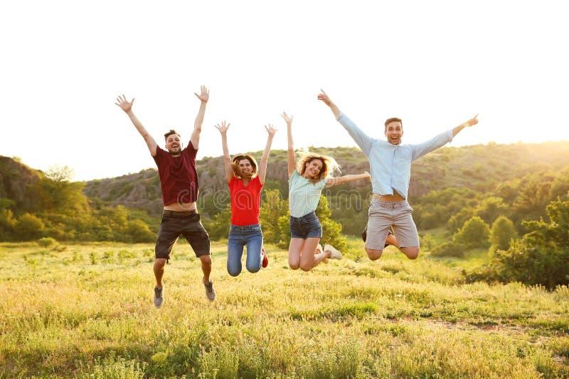 Счастливое молодые люди скача в глушь стоковое изображение