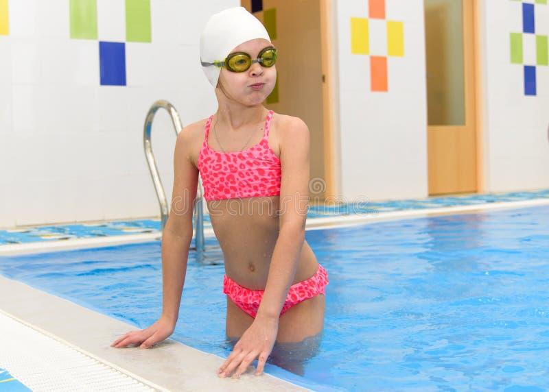Счастливое плавание маленькой девочки в бассейне Кавказский ребенок играет потеху в бассейне детского сада стоковые фото