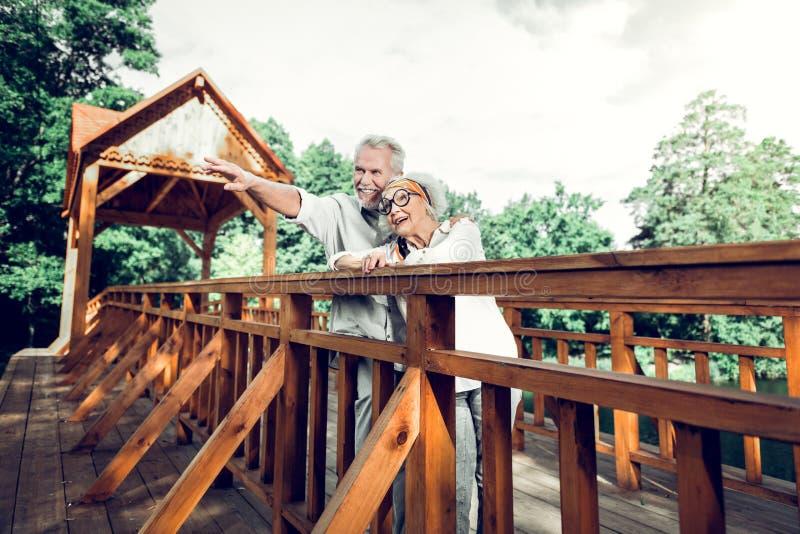 Счастливое положение пар на мосте и наслаждаться пейзажем природы стоковое изображение rf