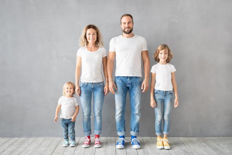 Счастливое положение семьи против серой предпосылки стоковые изображения rf