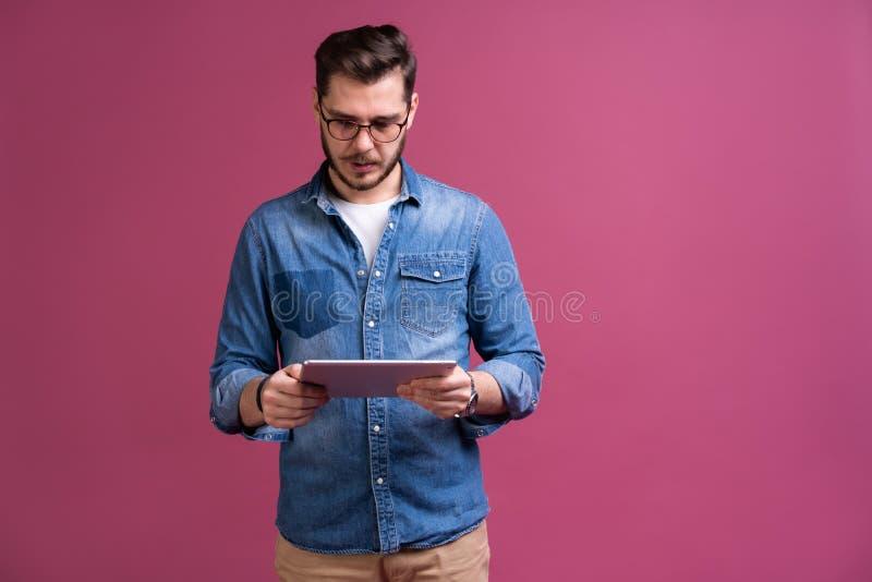 Счастливое привлекательное положение молодого человека и планшет использования над розовой предпосылкой стоковое фото