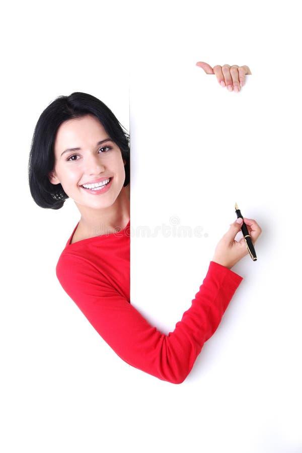 Счастливое сочинительство женщины с пер на пустой доске. стоковое фото rf