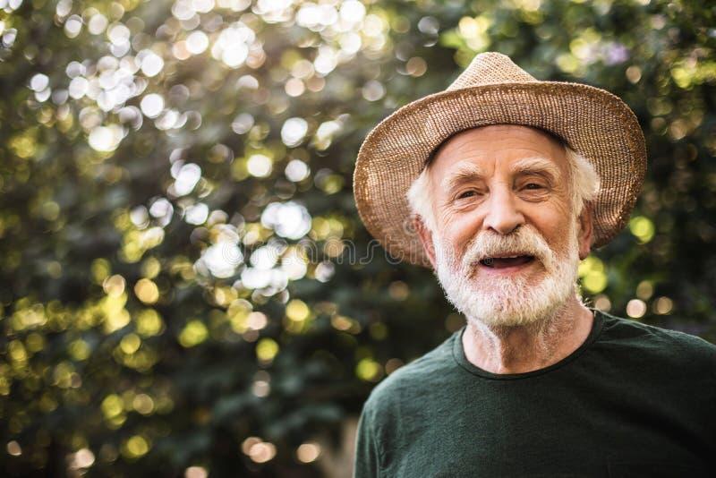 Счастливое старое деревенское положение человека в саде стоковая фотография