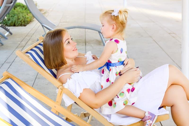 Счастливое усаживание матери и дочери, ослабляя в deckchair в рекреационной зоне парка города и имея togetther потехи Семья rec стоковая фотография