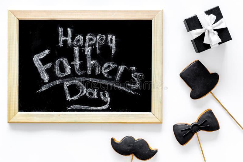 Счастливое утро дня ` s отца с черным галстуком, печенья усика и шляпы, подарочная коробка для празднуют белое взгляд сверху пред стоковые фото