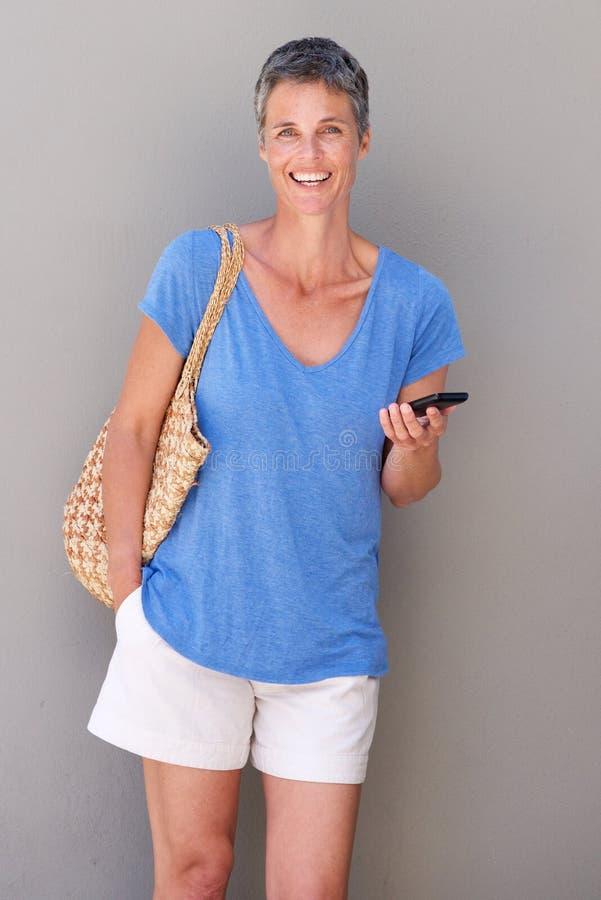 Счастливой женщина постаретая серединой держа мобильный телефон стоковое изображение rf