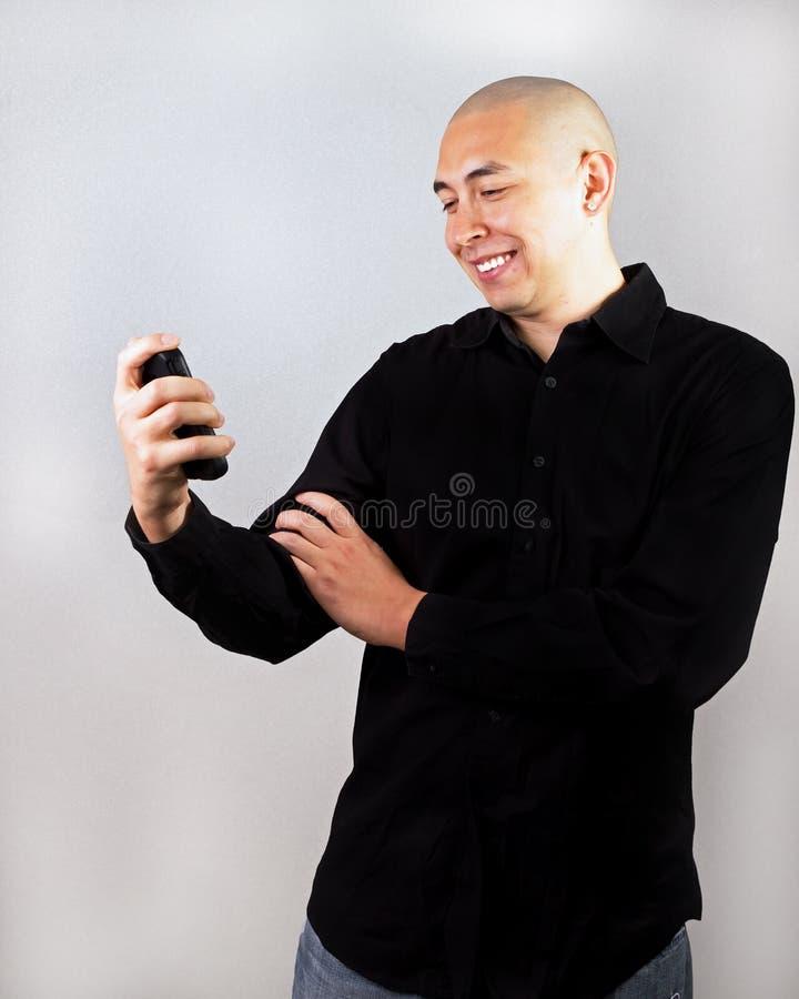 счастливо его смотря smartphone человека стоковое фото